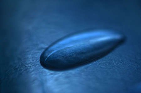 A close up of a drop of water on blue