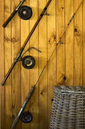 Three fishing rods on a textured wooden wall with a wicker fishermans basket underneath