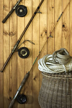 resting rod fishing: Antique fishing rods on a wooden wall with a wicker fishing basket and rope Stock Photo