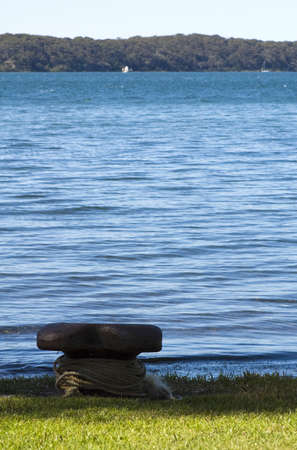A boat pylon on a grassy shore next to a calm lake Stock Photo - 5846553