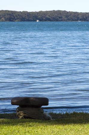 A boat pylon on a grassy shore next to a calm lake Stock Photo - 5846553
