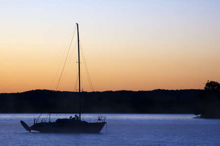 A sailboat silhouetted on the lake at sunrise photo