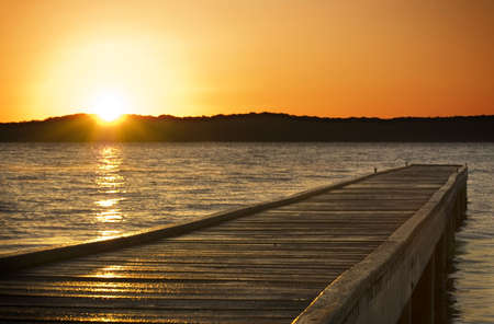 Une jetée de petite bâtonnets sur le lac au lever du soleil