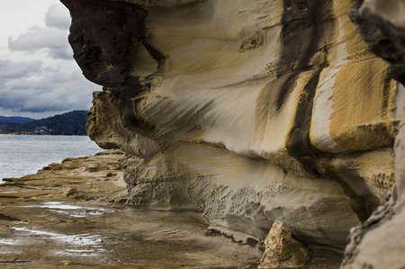 An eroded cliff face along a rough coastline photo