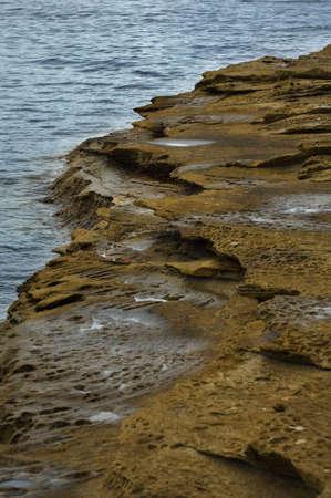 A rocky outcrop drops off into the ocean