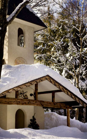 The exterior of a small church which is covered in snow
