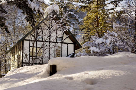 White tudor style cabin in the woods in winter covered in snow Stock Photo
