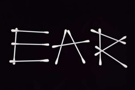 The word Ear written using cotton ear cleaning buds.  Isolated on black. Stock Photo
