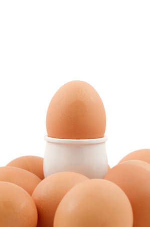 A brown egg in an eggcup surrounded by lots more eggs isolated on white. photo