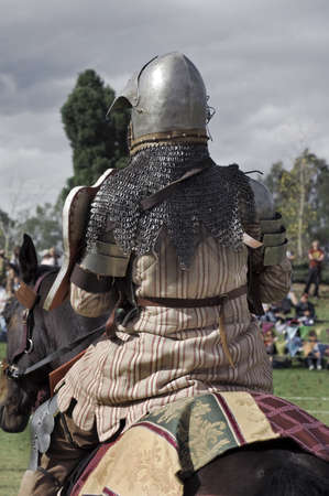 Medieval knight sitting on his horse. From behind.