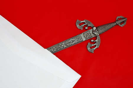 Highly detailed sword shaped letter opener opening a white envelope isolated on red Stock Photo