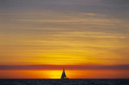 A sailboat on the horizon is silhouetted by the setting sun.