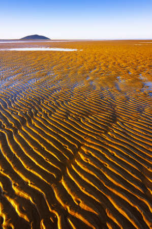 Ripple lines in the sand at low tide disappear into the distance.