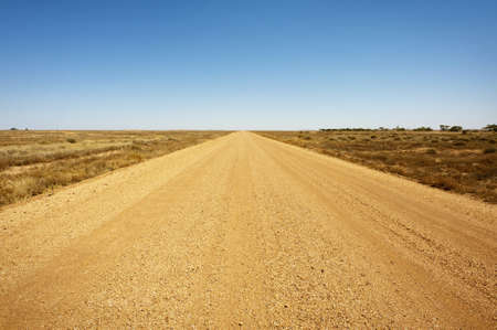 A long, straight dirt road disappears into the distant horizon. photo