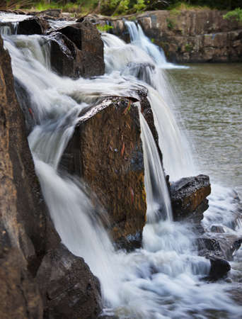 Close up image of a waterfall cascading over rocks. photo