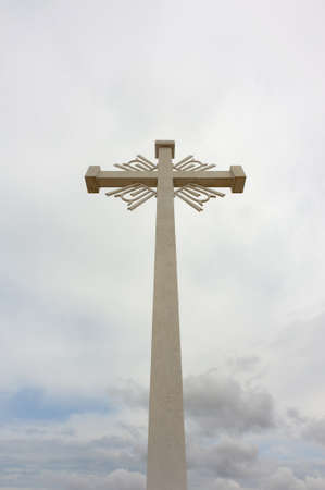 A large, white, decorative cross stands tall against an overcast sky. Stock Photo