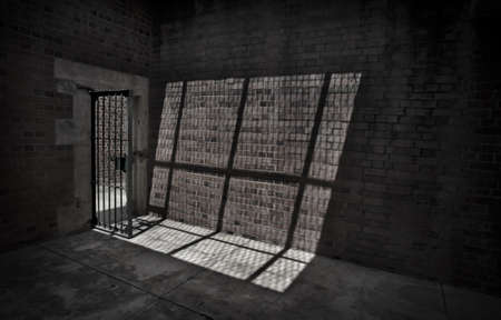 Sunlight shines through the barred door of a prison cell casting a shadow on the stone wall.