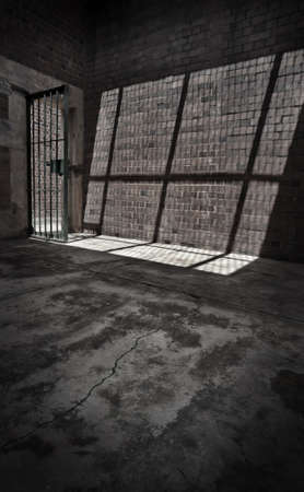 Sunlight shines through the barred door of a prison cell casting a shadow on the stone wall. photo