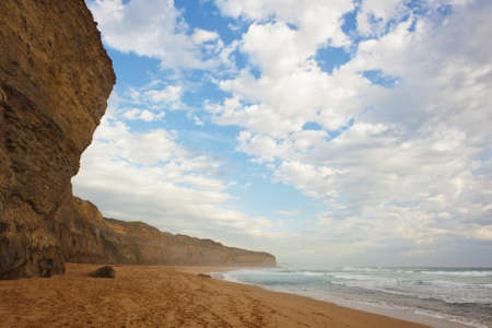 A huge cliff stands over a pristine sandy beach