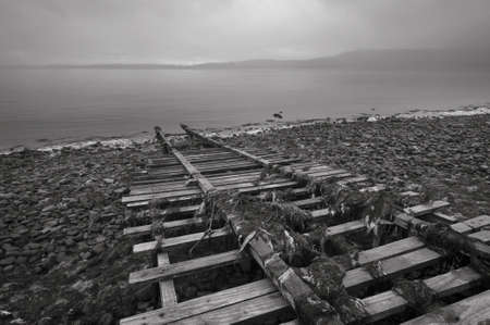 rickety: Old boat tracks lead into the lake   Black and white  Stock Photo