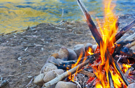 A hot campfire burns next to a river  Stock Photo - 20323950