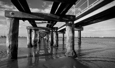 Underneath a crumbling, old pier on a calm day in black and white. photo