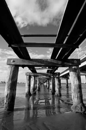 Underneath a crumbling, old pier on a calm day in black and white.