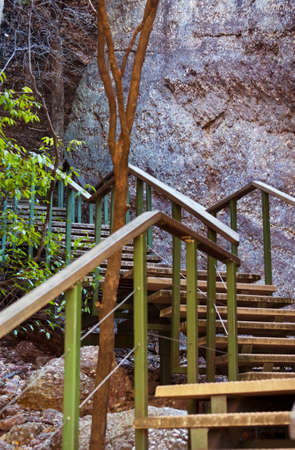 Wooden stairs leading up a rock face. photo