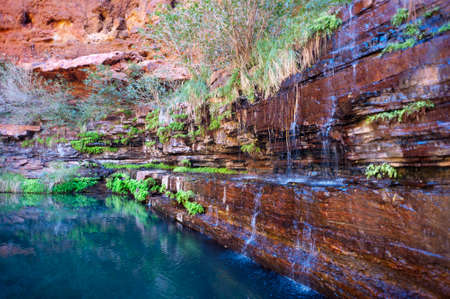 A small waterfall trickles down the rocks into a tropical blue waterhole  Stock Photo