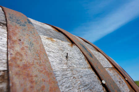 Close up of a wooden wine cask set against a blue sky  Stock Photo