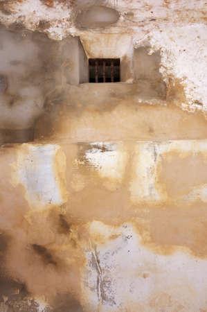 rejas de hierro: Y ventana de la c�rcel vieja, con barras de hierro, en lo alto de un muro de la prisi�n.