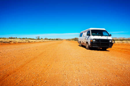 campervan: Backpacker campervan during a road trip on a dusty deserted road on a sunny day.