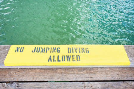 no diving sign: No diving sign painted onto a wooden pier. Stock Photo