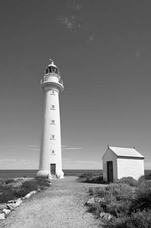 Close up of a tall, white lighthouse on a headland overlooking the coast in black and white.