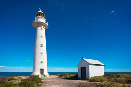 headland: Close up of a tall, white lighthouse on a headland overlooking the coast on a sunny day. Stock Photo