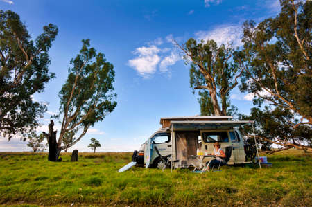A smiling woman relaxing outside her motorhome in a scenic location in the Australian bush.