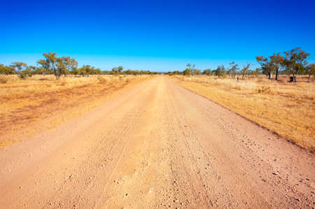 disappears: A long, straight dirt road disappears into the distant horizon. Stock Photo