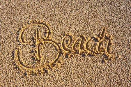 sommerferien: Das Wort Hand 'Beach' in den Sand geschrieben. Ferien-Konzept.