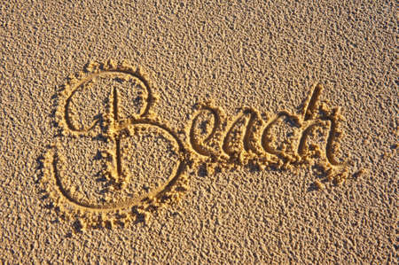 The word Beach hand written in the sand. Summer vacation concept. Stock Photo