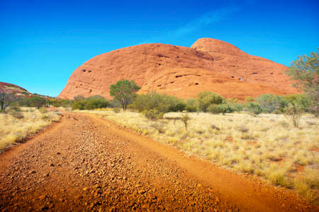 A dirt road leads through the Australian outback towards The Olgas in the Northern Territory.