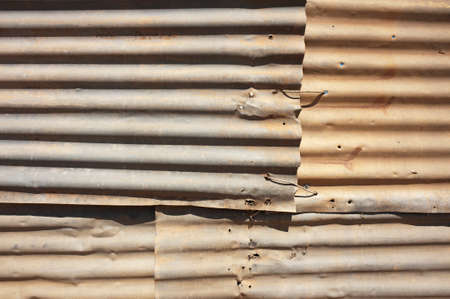 corrugated iron: Sheets of corrugated iron overlap in an old, roughly constructed tin wall.