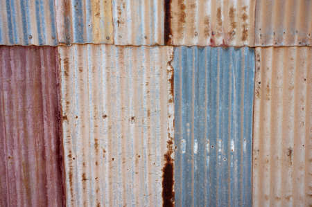 Sheets of colorful corrugated iron overlap in an old, roughly constructed tin wall. Stock Photo