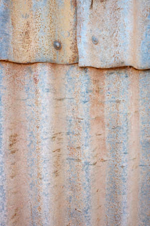 Close up of sheets of corrugated iron overlaping in an old, roughly constructed tin wall. Stock Photo