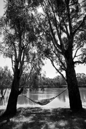 Silhouette of person relaxing in a hammock between two trees next to a river. Stock Photo
