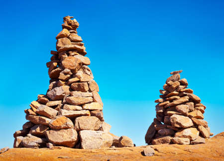 Two man made stone cairns on top of a mountain on a blue, sunny day.