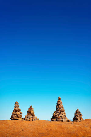 Four man made stone cairns on top of a mountain on a blue, sunny day.