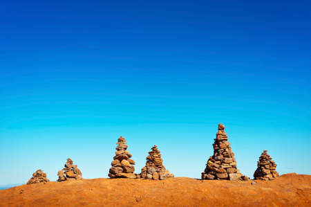 Six man made stone cairns on top of a mountain on a blue, sunny day.