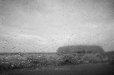 Looking at the iconic Uluru through a wet car window in Australias outback. Stock Photo