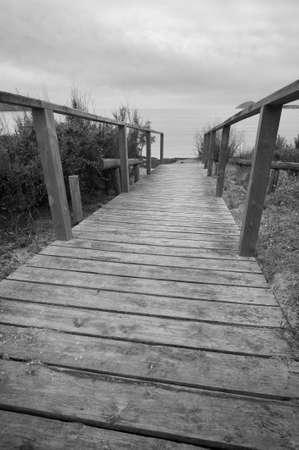 Wooden boardwalk to the beach. Black and white.