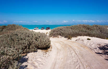 A 4WD track over sand dunes leads down to the beach and the tropical blue sea.